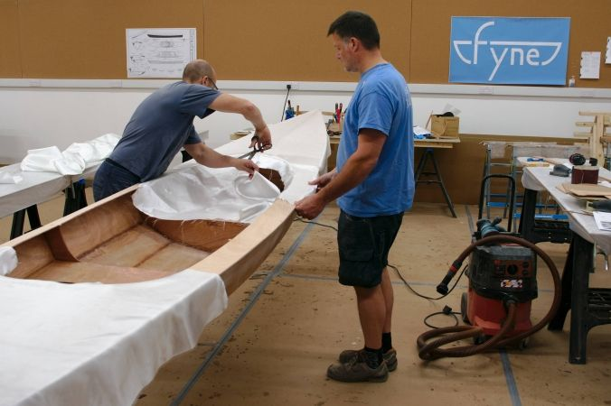 Fibreglassing the Expedition Wherry on a boatbuilding course at Fyne Boat Kits