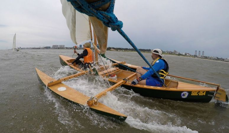 The Eureka canoe sailing with drop-in outriggers