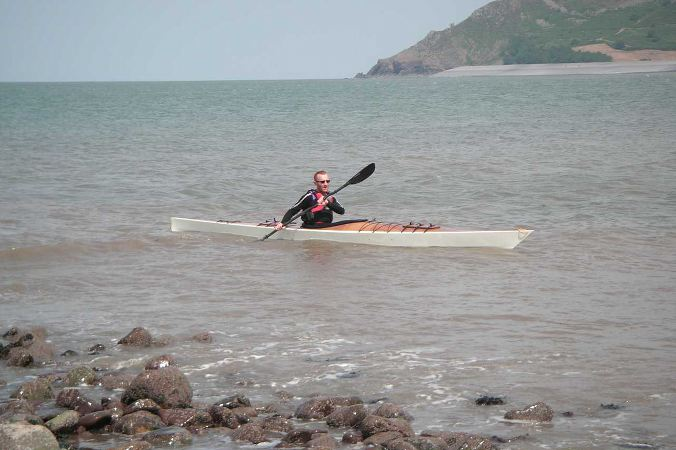 Home made wooden sea kayak near rocks