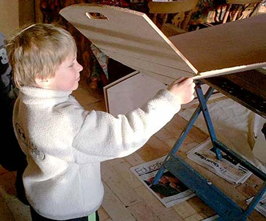 A boy building his first rowing boat from Fyne Boat Kits