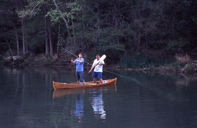 Fly fishing standing in a canoe built at home from plans