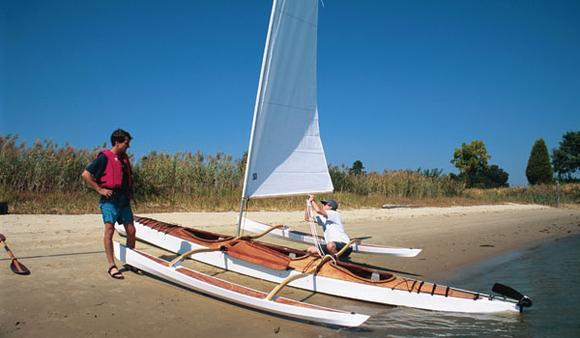 Sailing a triple wooden kayak with outriggers