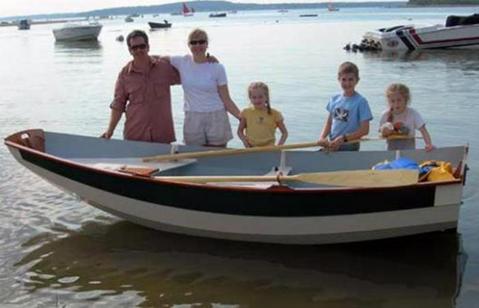 Proud family showing off the Passagemaker clinker rowing boat they built