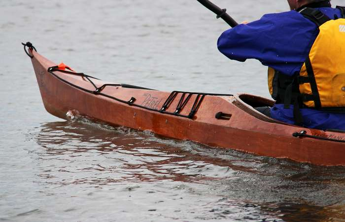 The deck shape of the Petrel wooden sea kayak provides knee room while remaining low
