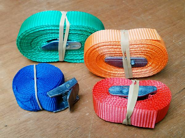 Webbing straps with cam buckles for securely lashing a boat to a roof rack or kayak trolley