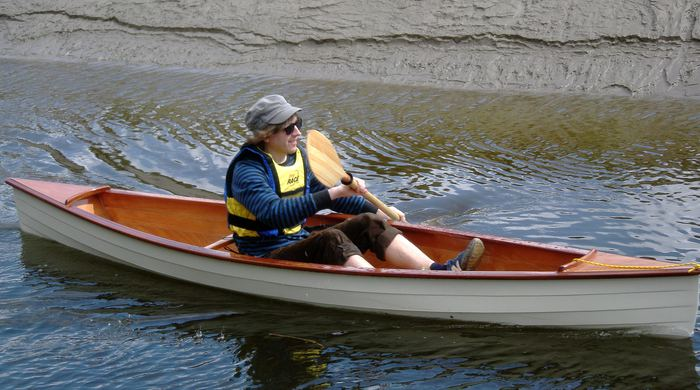 Single seat open canoe paddled by the proud builder