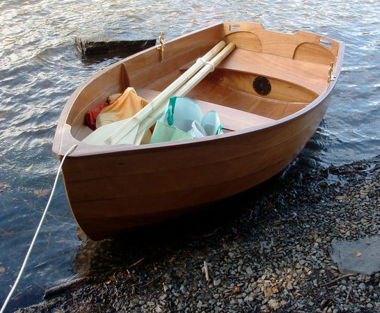 A wooden stem dinghy used as a tender to a yacht