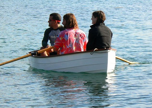 Three people in the stem dinghy as built from a kit