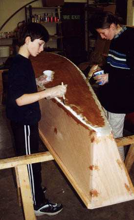 Children epoxy coating a canoe they have built