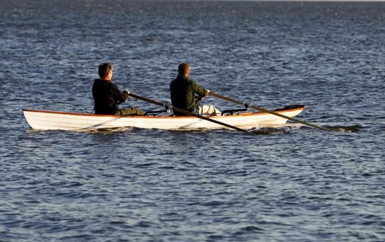 Two person clinker style rowing boat in rough water
