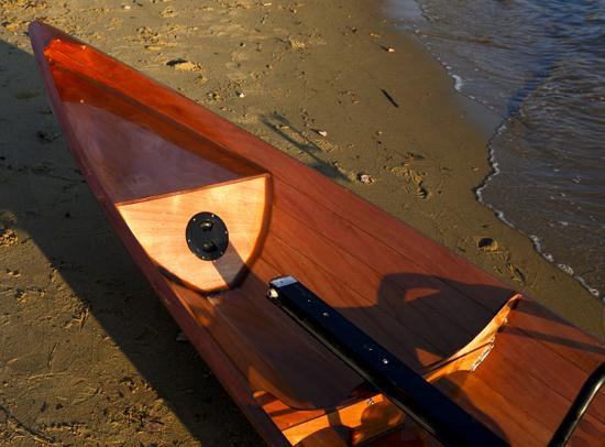 Shiny bow of a wooden wherry rowing boat that is built for two